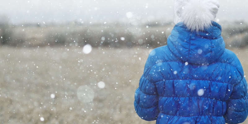 An Image of A Woman Wearing Blue Water Proof Jacket And White Scorf In A Winter Season.