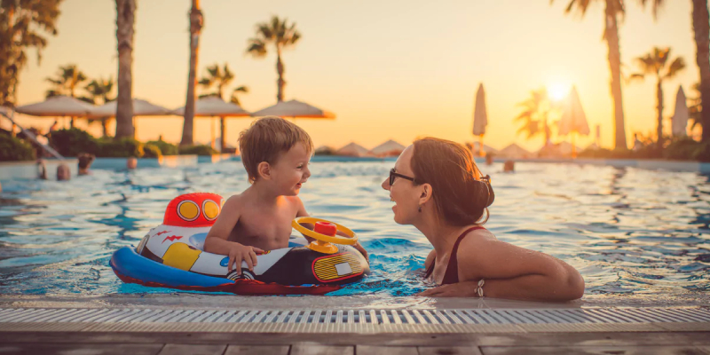 A Cute Little Boy Sitting In Pool Float & Busy Chatting With His Mom In The Pool.