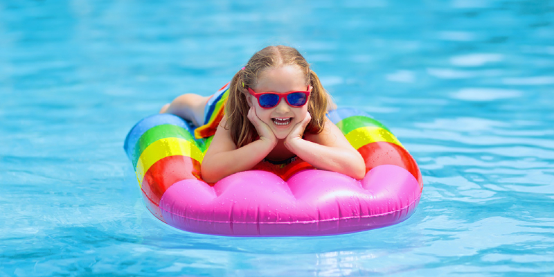 A Cute Adorable Little Girl Wearing Sun Glasses Giving Pose For The Camera From The Pool Float.