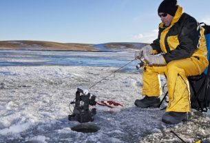 A Man Sitting And Hunting Ice Fish.
