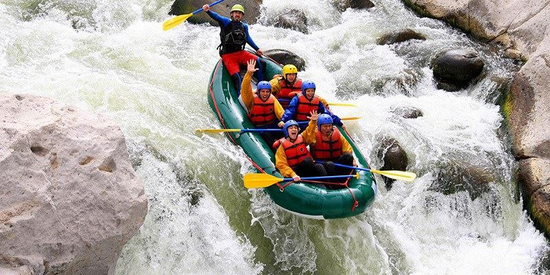 Group of Young People Enjoying While In River Rafting.