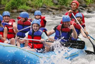 Group of Happy People While In River Rafting.